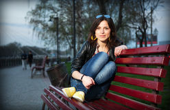 Muchacha en un parque de la ciudad en un banco Foto de archivo libre de regalías