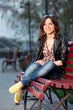 Muchacha en un parque de la ciudad en un banco Imagen de archivo