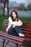 Muchacha en un parque de la ciudad en un banco Imágenes de archivo libres de regalías
