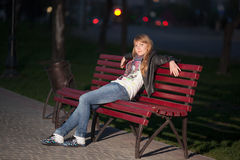 Muchacha en un parque de la ciudad en un banco Foto de archivo