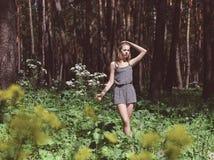 Muchacha en un parque del pino en el verano Imagenes de archivo