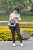 Muchacha en un parque ocupado con su teléfono elegante, Pekín, China Imagen de archivo libre de regalías