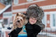 Muchacha en un paseo escarchado de la tarde del invierno del sombrero de piel con su terrier de Yorkshire querido del perro Fotos de archivo