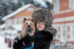 Muchacha en un paseo escarchado de la tarde del invierno del sombrero de piel con su terrier de Yorkshire querido del perro Imagen de archivo libre de regalías