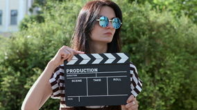 Muchacha en un patio verde del verano con la tablilla adentro almacen de metraje de vídeo