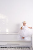Muchacha en un piano blanco Fotos de archivo