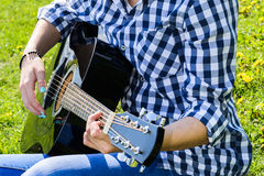 Muchacha en un prado verde que toca la guitarra Imagen de archivo libre de regalías
