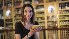 Muchacha en un restaurante con una taza de café, disfrutando del aroma y del sabor del café mientras que se relaja en la cafeterí almacen de video