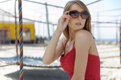 Muchacha en un rojo en la playa Imagenes de archivo