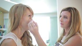 Muchacha en un salón de belleza artista de maquillaje y peluquero que trabajan en una mujer almacen de video