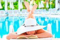 Muchacha en un sillón cerca de la piscina y de leer una novela romántica imagenes de archivo
