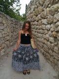 Muchacha en un smilinig largo de la falda cerca de la pared de piedra Fotografía de archivo libre de regalías