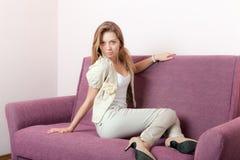 Muchacha en un sofá Foto de archivo libre de regalías