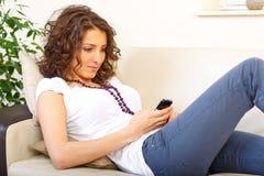 Muchacha en un sofá usando un teléfono móvil Imagen de archivo libre de regalías