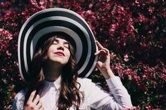Muchacha en un sombrero en árboles florecientes Imagenes de archivo
