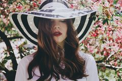 Muchacha en un sombrero en árboles florecientes Fotografía de archivo