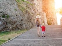 Muchacha en un sombrero con un hijo joven que camina cerca de las paredes de la fortaleza, luz del sol Visión posterior Fotografía de archivo