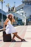 Muchacha en un sombrero con una maleta que va en resto Fotos de archivo