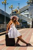 Muchacha en un sombrero con una maleta que va en resto Imagen de archivo