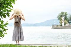 Muchacha en un sombrero con una mochila que se coloca en un embarcadero en el mar Montañas y faro en el fondo Visión desde la par Foto de archivo