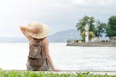 Muchacha en un sombrero con una mochila que se sienta en el embarcadero Montañas y faro en el fondo Visión desde la parte posteri Fotografía de archivo libre de regalías