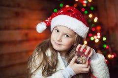 Muchacha en un sombrero de la Navidad con un presente Fotos de archivo