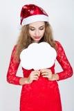 Muchacha en un sombrero de la Navidad que sostiene banderas bajo la forma de nubes Foto de archivo
