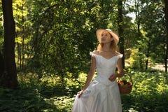 Muchacha en un sombrero de paja en el bosque en un día soleado fotografía de archivo libre de regalías