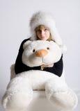 Muchacha en un sombrero de piel con un oso Imagenes de archivo