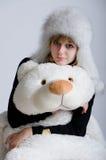 Muchacha en un sombrero de piel con un oso Foto de archivo
