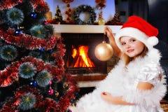 Muchacha en un sombrero de Santa que adorna el árbol de navidad Imagenes de archivo