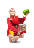 Muchacha en un sombrero de santa que se sienta con los regalos de la Navidad Imagenes de archivo