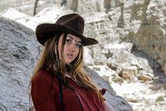 Muchacha en un sombrero de vaquero que se coloca en los acantilados blancos Imagenes de archivo