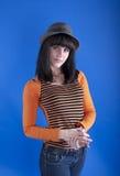 Muchacha en un sombrero en un fondo azul imagenes de archivo