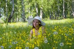 muchacha en un sombrero en un prado entre las flores y los dientes de león amarillos Fotografía de archivo