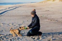 Muchacha en un sombrero hecho punto que juega con un perro en la playa Fotos de archivo