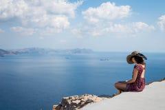Muchacha en un sombrero que se sienta al borde de la montaña que hace frente al mar Foto de archivo libre de regalías