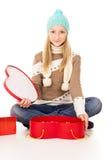 Muchacha en un sombrero que se sienta con los rectángulos de regalo Fotografía de archivo