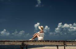 Muchacha en un sombrero que se sienta en un puente de madera maldives Arena blanca Fotos de archivo libres de regalías