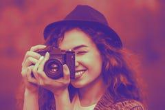 Muchacha en un sombrero que sonríe y que fotografía la naturaleza Imágenes de archivo libres de regalías