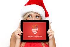 Muchacha en un sombrero rojo de la Navidad en la tableta de la tenencia del Año Nuevo con chri Fotografía de archivo libre de regalías