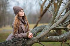 Muchacha en un sombrero y una bufanda hechos punto en un árbol caido en la caída en la naturaleza Imágenes de archivo libres de regalías