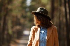 Muchacha en un sombrero y una capa en el fondo del bosque imagenes de archivo
