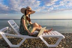 Muchacha en un sombrero y un vestido, en un funcionamiento del sillón en el ordenador, independiente, contra el mar fotos de archivo libres de regalías