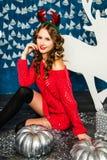 Muchacha en un suéter rojo que se sienta con los regalos de la Navidad Estafa del Año Nuevo Fotos de archivo