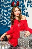 Muchacha en un suéter rojo que se sienta con los regalos de la Navidad Estafa del Año Nuevo Imagenes de archivo