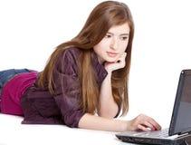 Muchacha en un suelo con la computadora portátil Foto de archivo libre de regalías