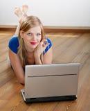 Muchacha en un suelo de madera con una computadora portátil Fotografía de archivo libre de regalías
