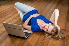 Muchacha en un suelo de madera con una computadora portátil Imagen de archivo