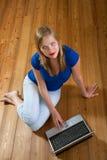 Muchacha en un suelo de madera que relaja y que usa una computadora portátil Fotos de archivo libres de regalías